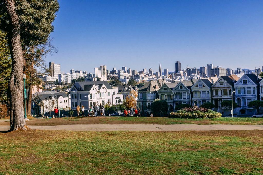 Painted Ladies bei Sonnenschein und der Skyline von San Francisco im Hintergrund